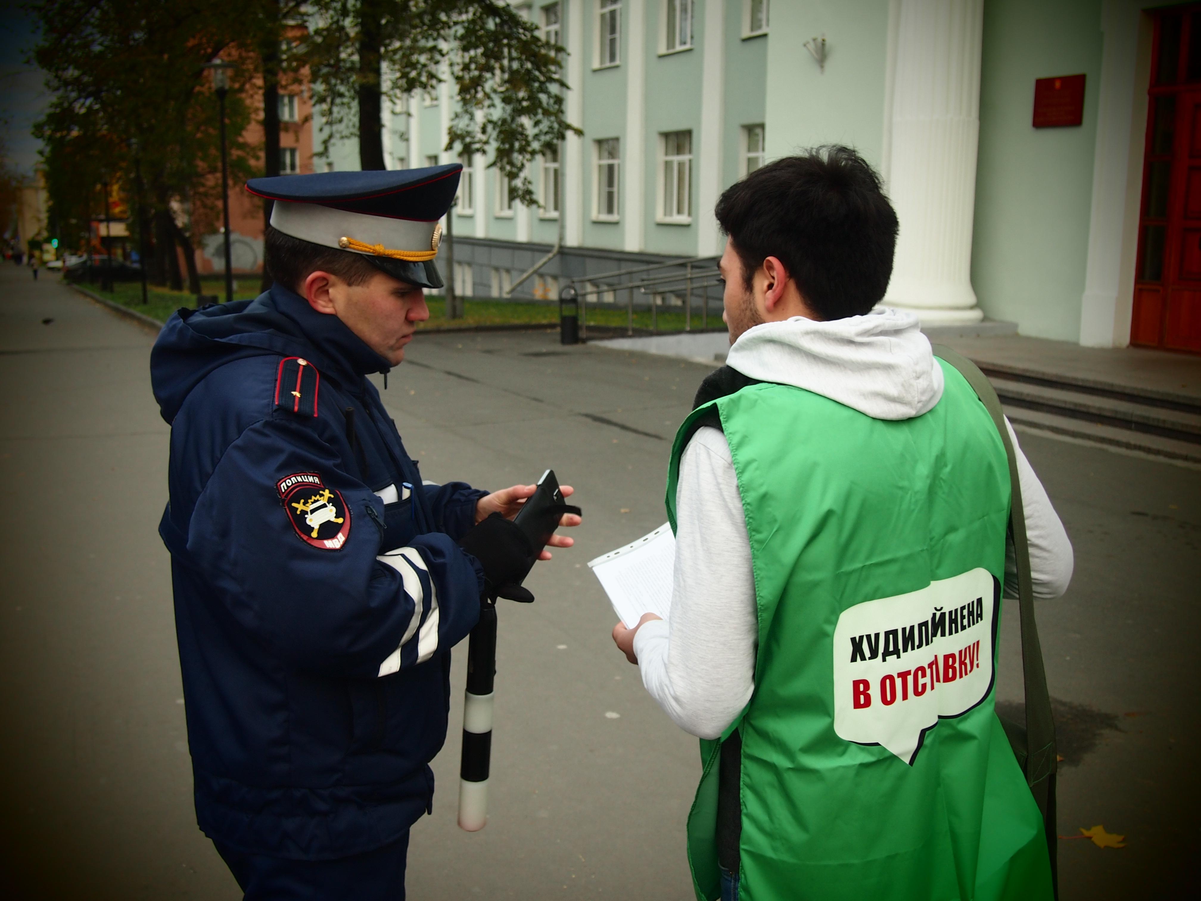 Сотрудник полиции выясняет личность сборщика подписей. Фото: Валерий Поташов
