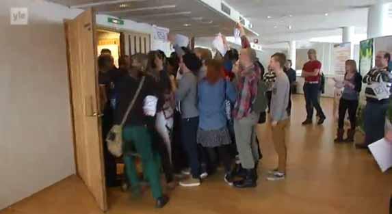 Демонстранты пытаются попасть в зал, где выступает премьер-министр Финляндии. Фрагмент репортажа финской телекомпании Yle