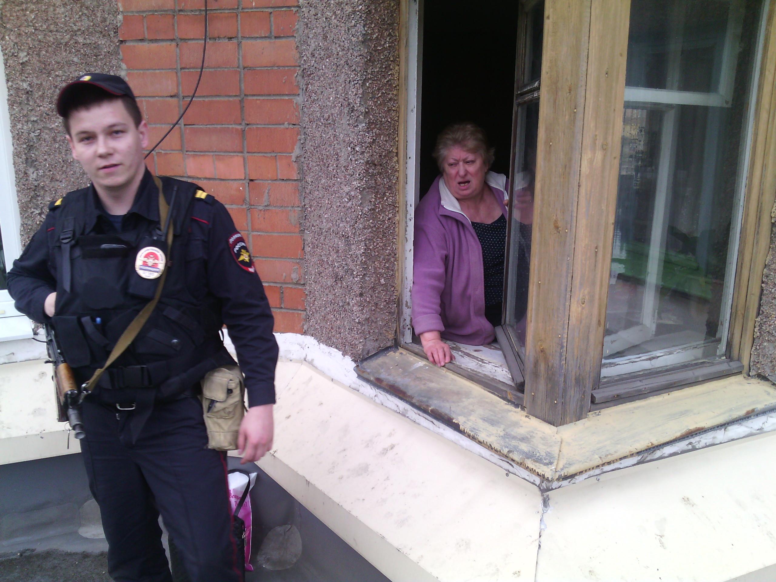 Сотрудник полиции возле окна одного из жильцов дома, требующих сноса незаконной пристройки. Фото: Валерий Поташов
